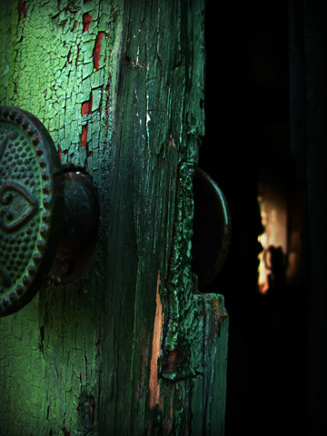 Mysterious weathered old door partially open revealing a strange light inside