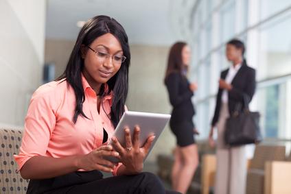tablet, two business women talking in background