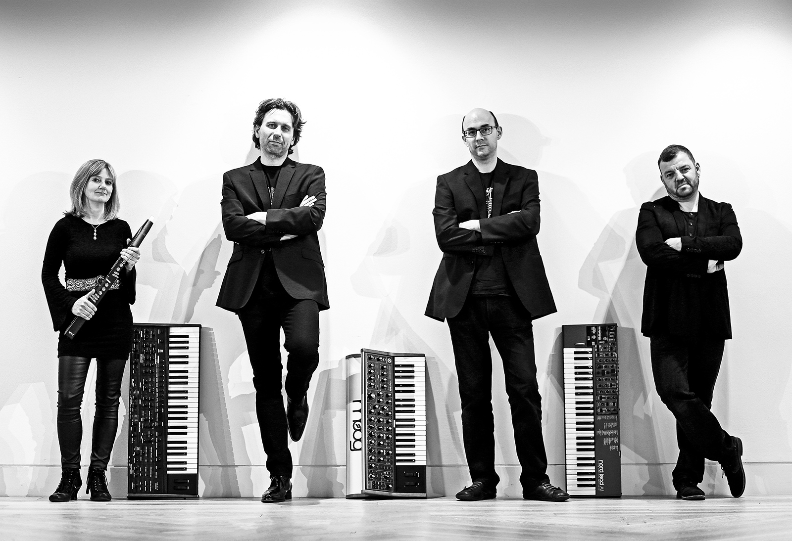 Art of Moog members standing against a wall with synthesizers between them
